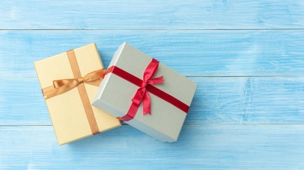 Caixa de presente de prata e ouro em uma mesa de madeira azul. Foto Premium