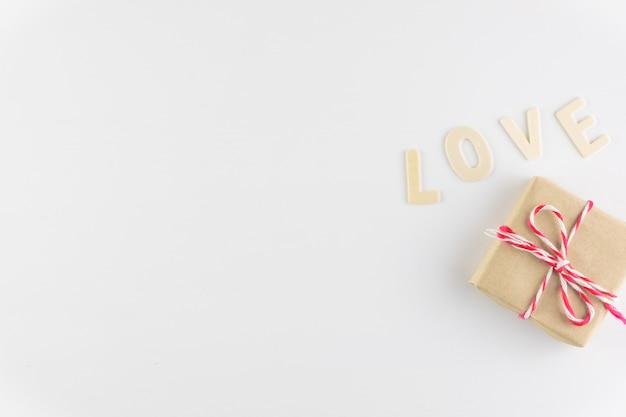 Caixa de presente e a palavra amor no fundo branco, com espaço para texto, dia dos namorados Foto Premium