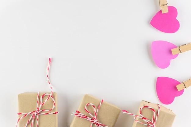 Caixa de presente e corações cor-de-rosa do amor no fundo de madeira branco, dia de valentim feliz. Foto Premium