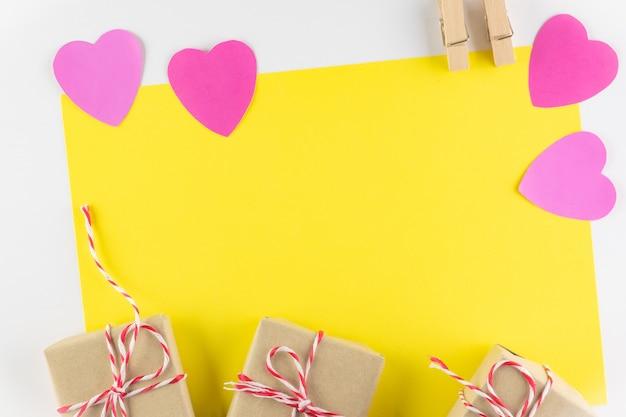 Caixa de presente e corações de amor-de-rosa sobre fundo amarelo, feliz dia dos namorados Foto Premium