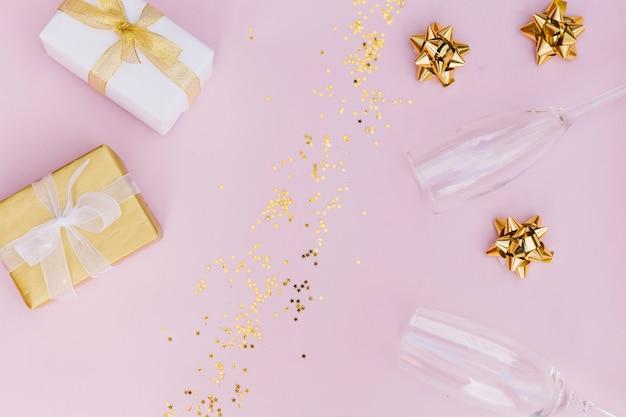 Caixa de presente embrulhada com arco; confete dourado; óculos de proa e champanhe no fundo rosa Foto gratuita