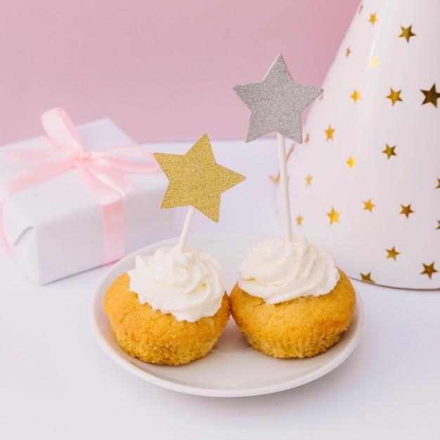 Caixa de presente embrulhado; chapéu de festa e cupcake com estrela de ouro e prata na mesa branca Foto gratuita