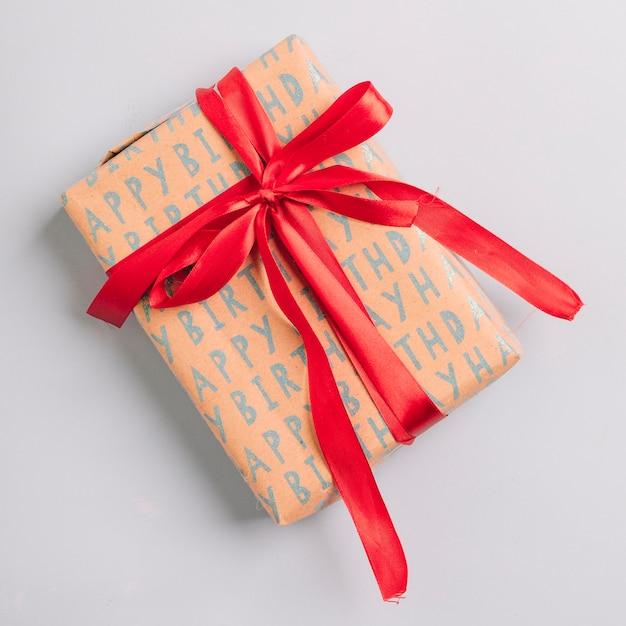 Caixa de presente embrulhado com fita vermelha como um feliz aniversário presente no fundo branco Foto gratuita