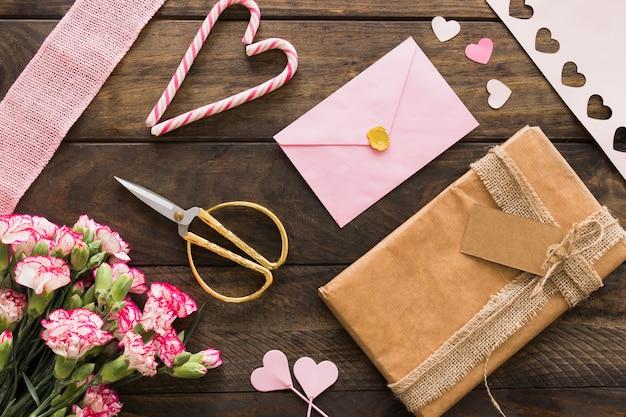 Caixa de presente entre flores, envelope e bastões de doces Foto gratuita