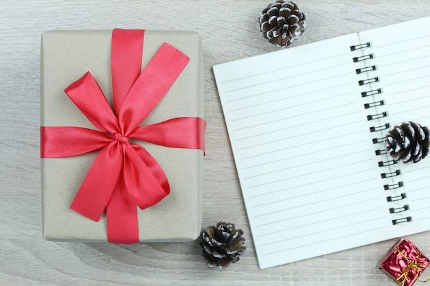 Caixa de presente marrom com laço vermelho no chão de madeira e livro em branco no natal e ano novo conce Foto Premium