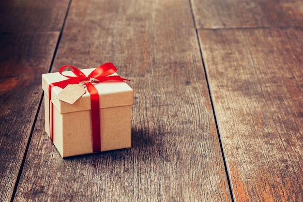 Caixa de presente marrom e fita vermelha com etiqueta em fundo de madeira com espaço. Foto Premium