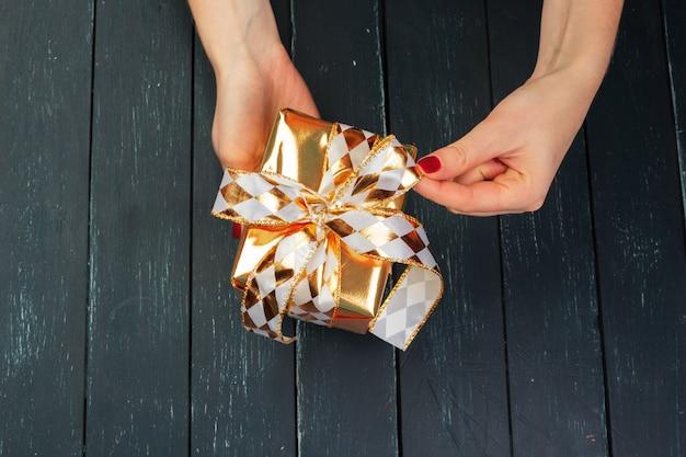 Caixa de presente na mão meninas na mesa de madeira Foto Premium