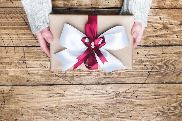 Caixa de presente ou presente com um grande laço nas mãos de uma mulher em um suéter. composição plana leiga para o natal, aniversário, dia das mães ou casamento. Foto Premium