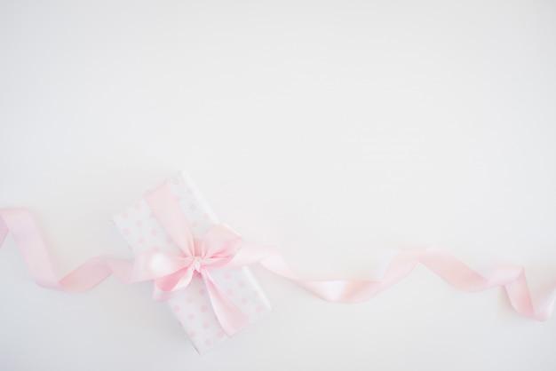 Caixa de presente para mulher - papel de bolinhas, laço rosa, pequenas flores Foto Premium