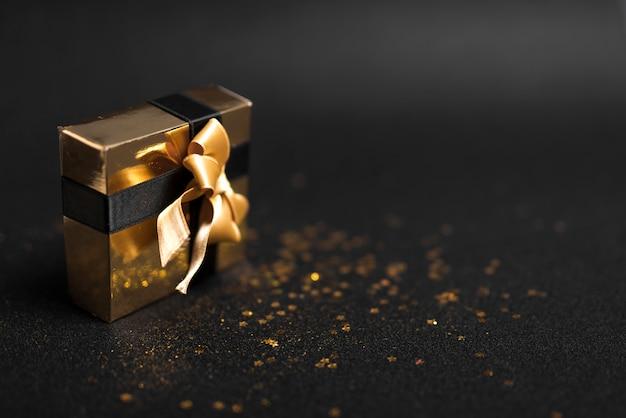Caixa de presente pequena com lantejoulas brilhantes na mesa Foto gratuita