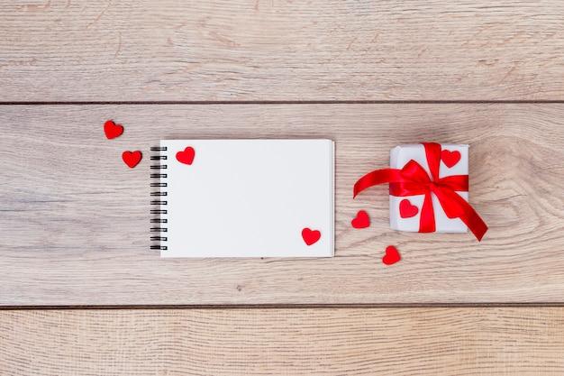 Caixa de presente pequena com o bloco de notas e corações na mesa Foto gratuita