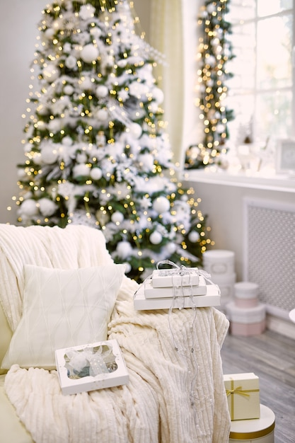 Caixa de presente perto da árvore de natal decorada na sala de estar Foto Premium