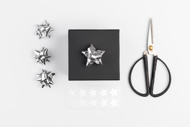 Caixa de presente perto de arcos e tesouras decorativas Foto gratuita