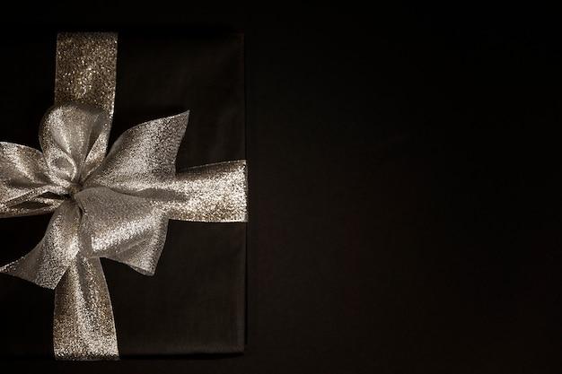Caixa de presente preta com um laço de prata sobre um fundo preto. cartão. espaço para texto. Foto Premium