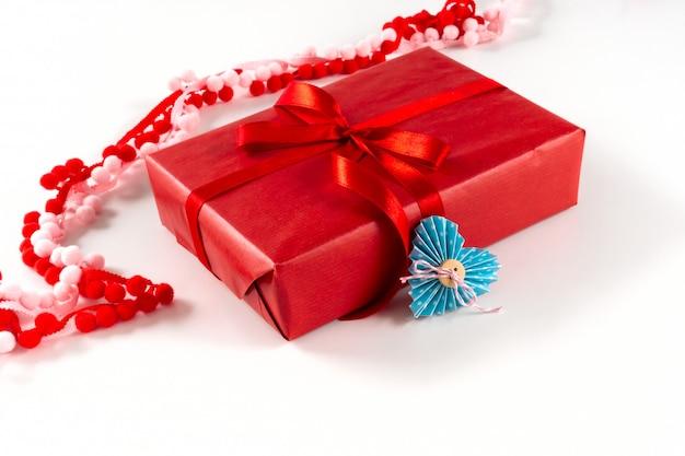 Caixa de presente vermelha com coração e laço em fundo branco. dia dos namorados 14 de fevereiro conceito de embalagem. Foto Premium
