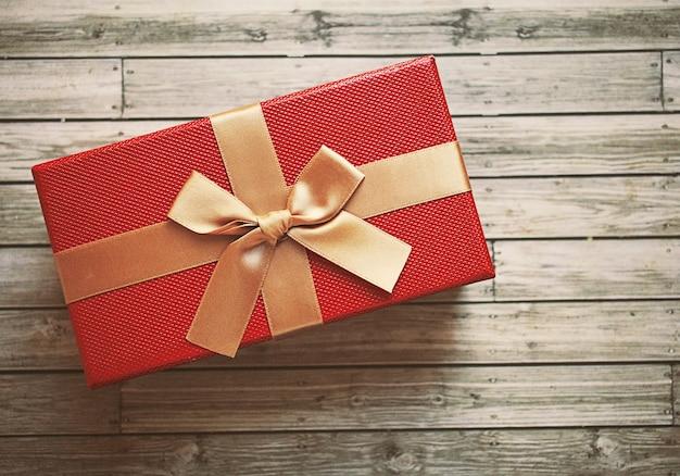 Caixa de presente vermelha com fita de ouro, efeito de filtro retro Foto gratuita