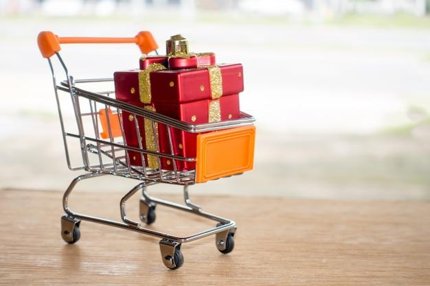 Caixa de presente vermelha em um carrinho de compras na tabela de madeira compra em linha do conceito. Foto Premium