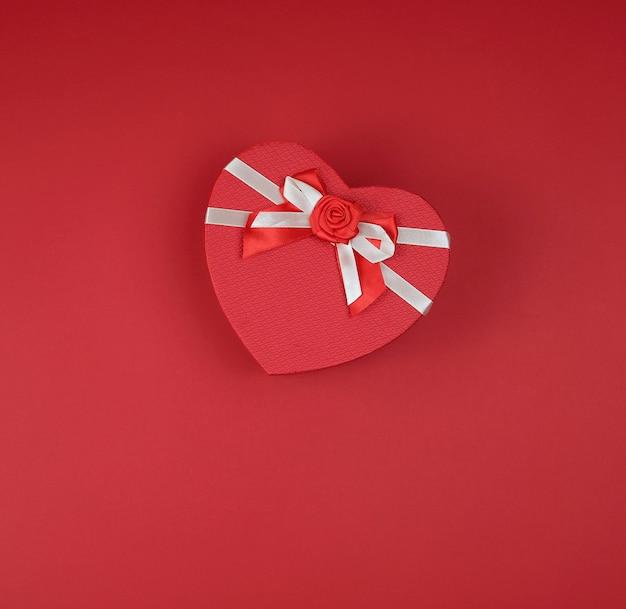 Caixa de presente vermelha na forma de um coração com um laço Foto Premium