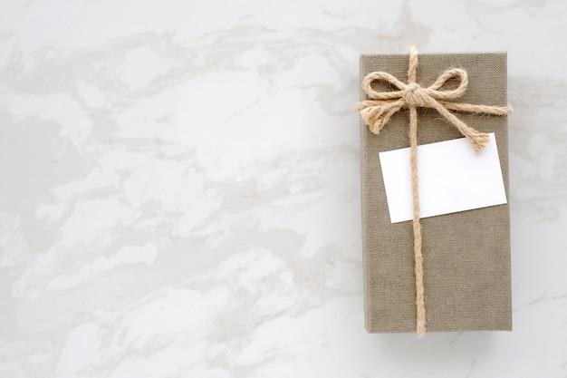 Caixa de presente vintage verde com cartão branco em branco e vaso de flores no fundo de mármore branco com espaço na cópia, vista superior, piso Foto Premium