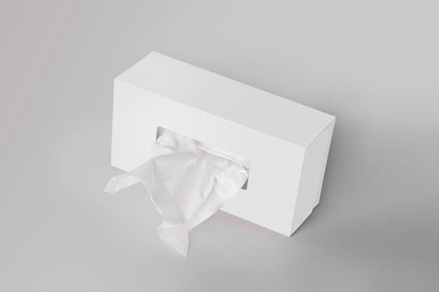 Caixa de tecido branco em branco sobre fundo cinza com tecido facial Foto Premium