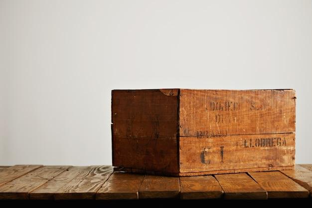 Caixa de vinho de madeira rústica marrom com letras pretas pouco legíveis em uma mesa de madeira contra o fundo da parede branca Foto gratuita