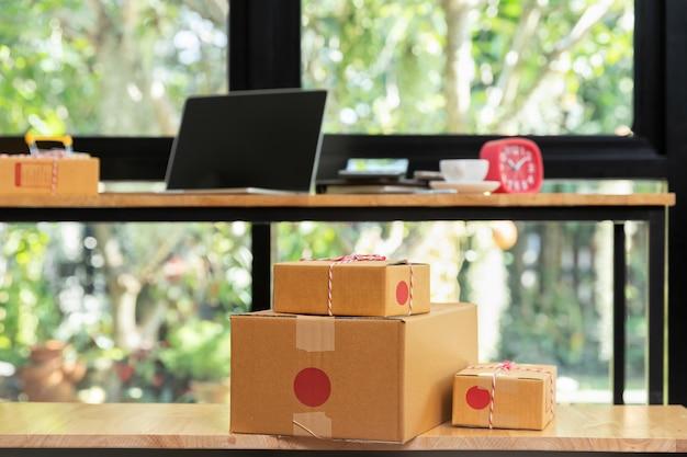 Caixa do pacote do cartão e portátil na mesa para a venda em linha. Foto Premium