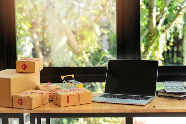 Caixa e portátil do pacote do cartão na mesa no local de trabalho para a venda em linha. Foto Premium