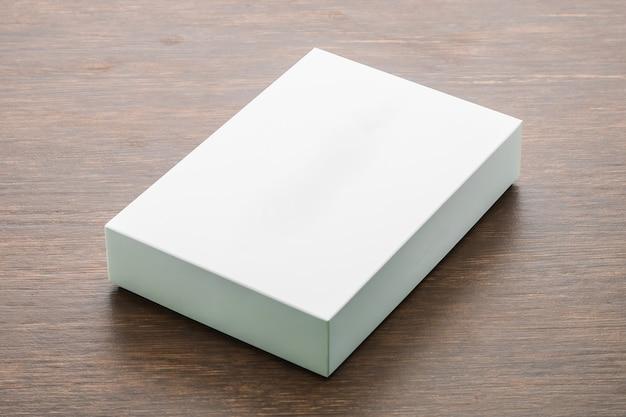 Caixa em branco simulada acima no fundo de madeira Foto gratuita
