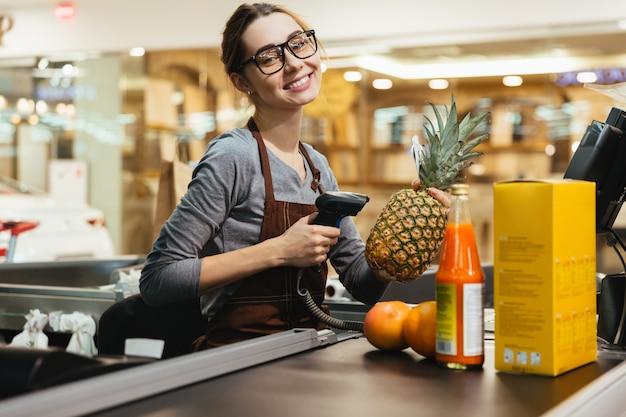 Caixa feminina feliz digitalização itens de mercearia Foto gratuita
