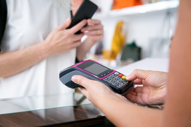 Caixa operacional do processo de pagamento, pressionando botões no terminal pos enquanto o cliente segura o smartphone. tiro recortado, close-up das mãos. conceito de compra ou compra Foto gratuita