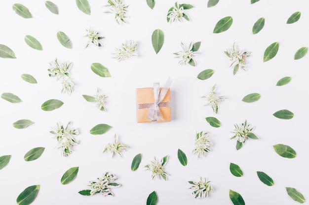Caixa pequena com um presente e fita em uma mesa branca Foto Premium