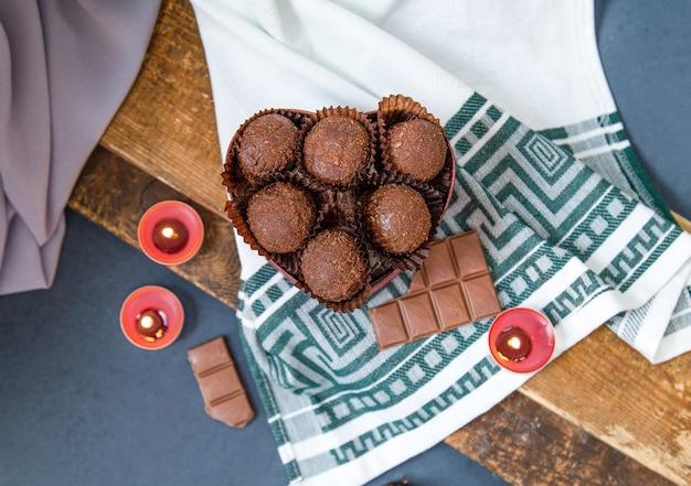 Caixa vermelha de chocolates, barra de chocolate com leite e velas flamejantes na toalha da mesa Foto gratuita