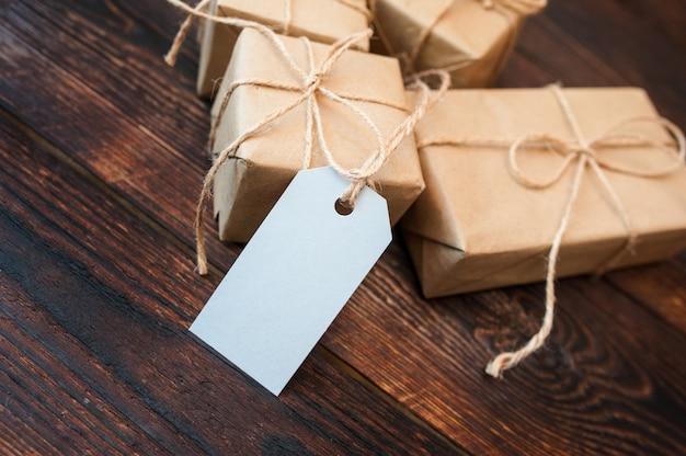Caixas de maquete para presentes de etiquetas de papel e presente de embalagem em uma superfície de madeira Foto Premium