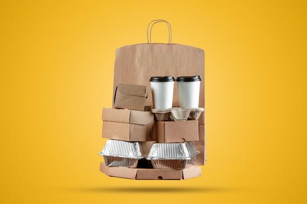 Caixas de pizza e saco de papel de entrega de comida com uma xícara de café descartável e uma caixa de wok em um fundo amarelo Foto Premium