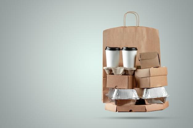 Caixas de pizza e saco de papel de entrega de comida com uma xícara de café descartável e uma caixa de wok em um fundo azul Foto Premium