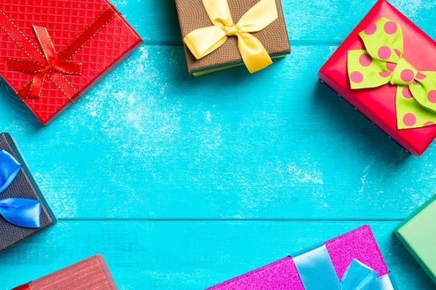 Caixas de presente colorida com fitas sobre fundo azul de madeira legal. Foto Premium