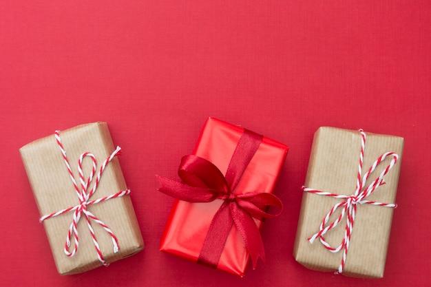 Caixas de presente de artesanato sobre fundo vermelho. simulado de natal com espaço de cópia. Foto Premium