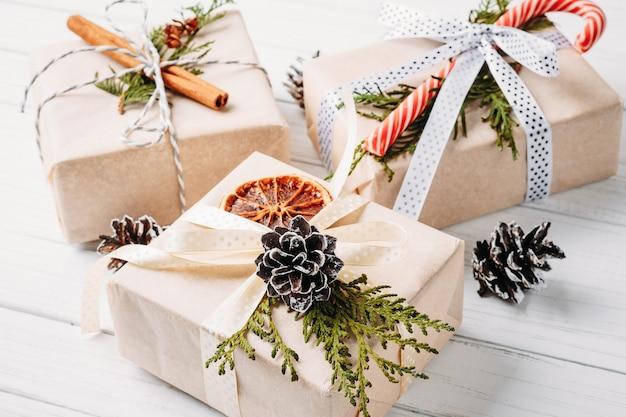 Caixas de presente de natal e decorações em um branco de madeira Foto Premium