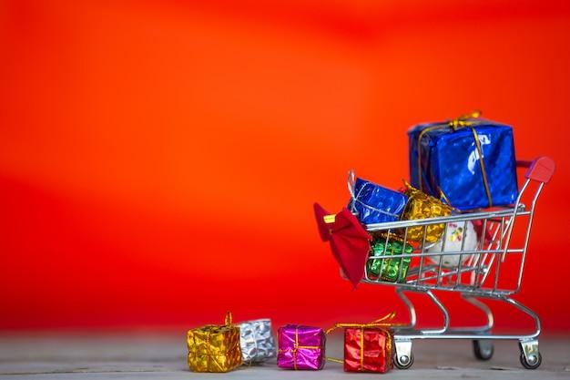 Caixas de presente de natal em várias cores, colocadas em um carrinho de compras Foto gratuita