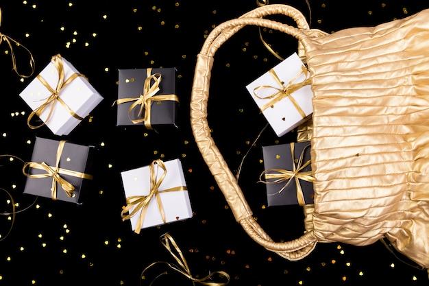 Caixas de presente em preto e branco com fita dourada saem da bolsa dourada na superfície de brilho, Foto Premium