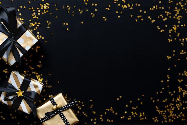 Caixas de presente em vários papéis de embrulho padrão ouro sobre estrela em forma de lantejoulas douradas sobre um fundo preto. Foto Premium