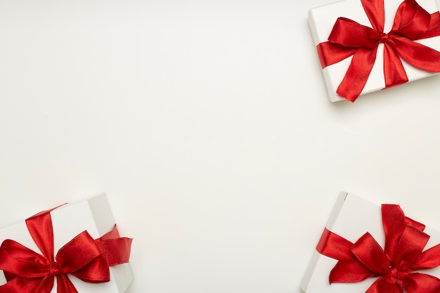Caixas de presente festivas com laços vermelhos Foto Premium