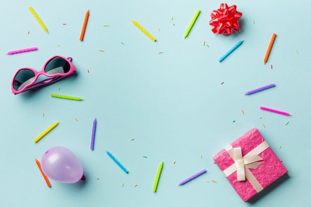 Caixas de presente; oculos escuros; laço de fita; balão; velas coloridas e granulado em fundo azul Foto gratuita