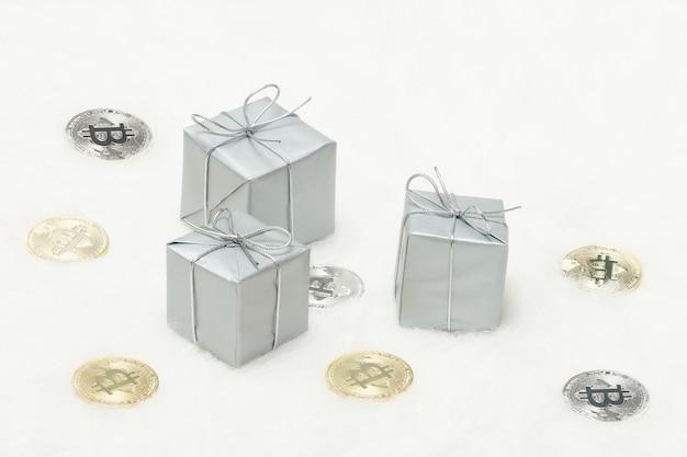 Caixas de presente prateado e moedas de bitcoins em um fundo branco Foto Premium
