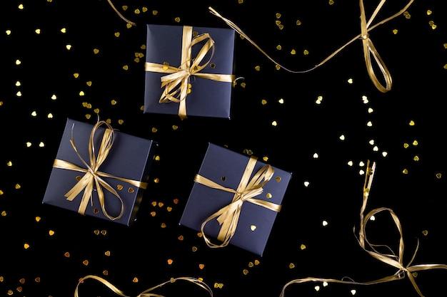 Caixas de presente preto com fita de ouro no brilho. postura plana. Foto Premium