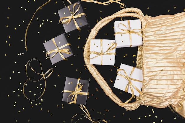 Caixas de presente preto e branco com fita de ouro saem da bolsa dourada no brilho. configuração plana Foto Premium