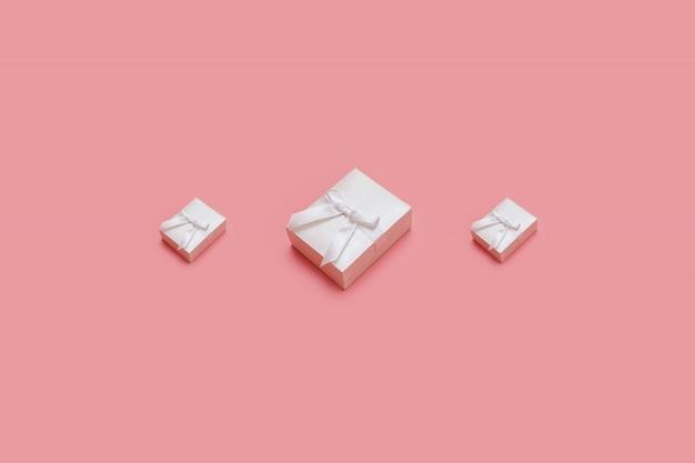 Caixas de presente rosa sobre fundo pastel. apresenta em estilo isométrico. presente de natal ou aniversário Foto Premium