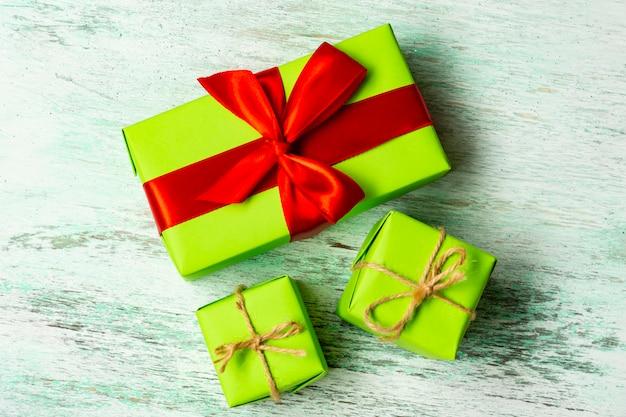 Caixas de presente verdes amarradas com barbante e onlight de fita vermelha de madeira. presente de natal. Foto Premium