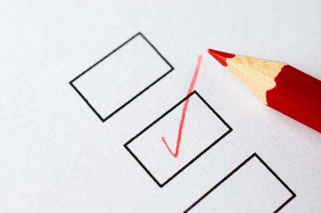 Caixas de seleção em um papel branco com lápis vermelho Foto Premium