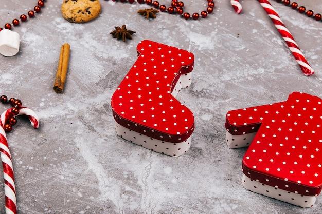 Caixas em forma de meias de natal e camisola deitado no chão cinza, cercado de biscoitos, especiarias e doces brancos vermelhos Foto gratuita